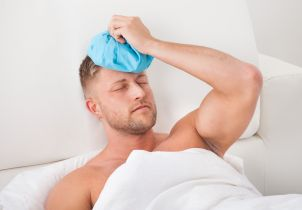 Man Nursing A Hangover Holding An Ice Pack